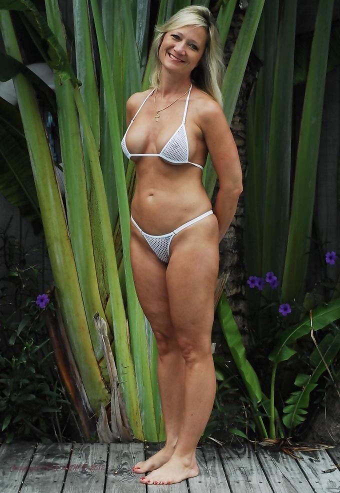 Portait Of Mature Woman Wearing Bikini Lying On A Jetty